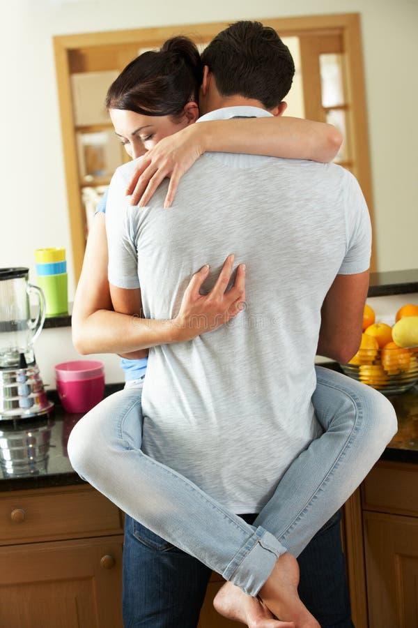 Romantiska par som kramar i kök fotografering för bildbyråer
