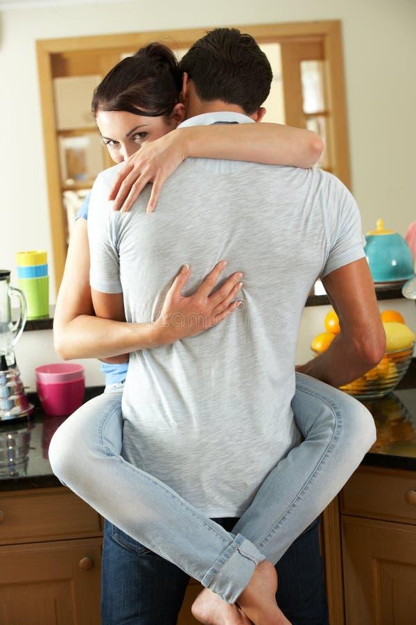 Romantiska par som kramar i kök arkivfoton