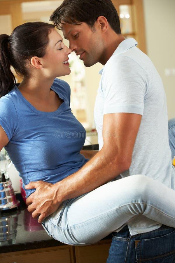 Romantiska par som kramar i kök royaltyfria bilder