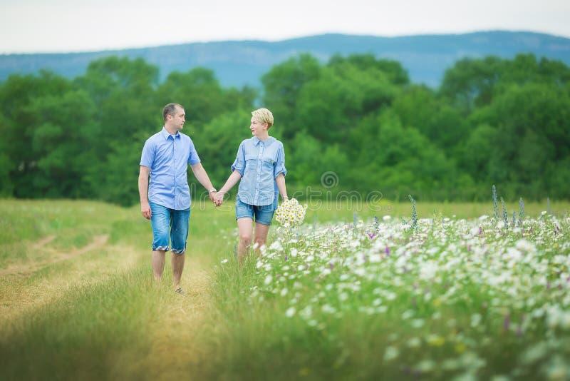 Romantiska par som kramar och andas ny luft i ett varmt fält med daizy blommor royaltyfri bild