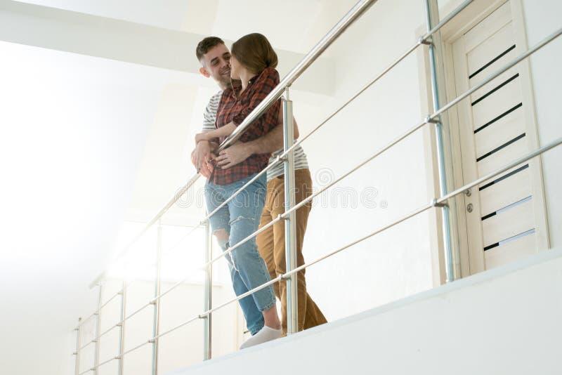 Romantiska par som kramar och kysser i korridor arkivbild
