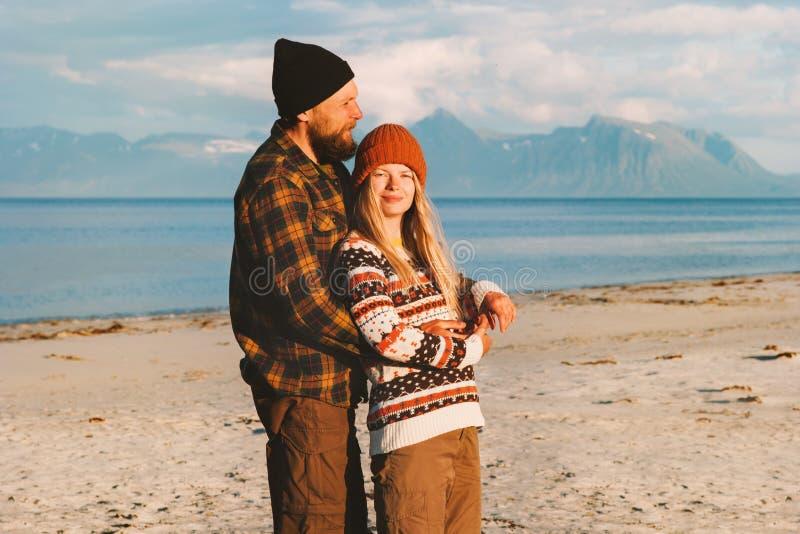 Romantiska par som kramar på stranden som tillsammans reser man- och kvinnafamiljen arkivbilder