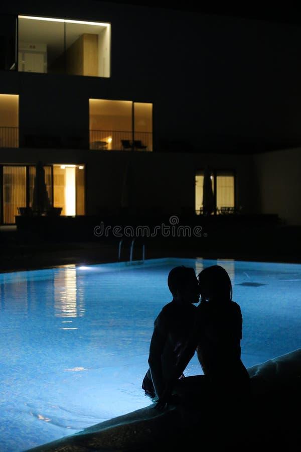 Romantiska par som kysser på pölen i natten arkivbilder