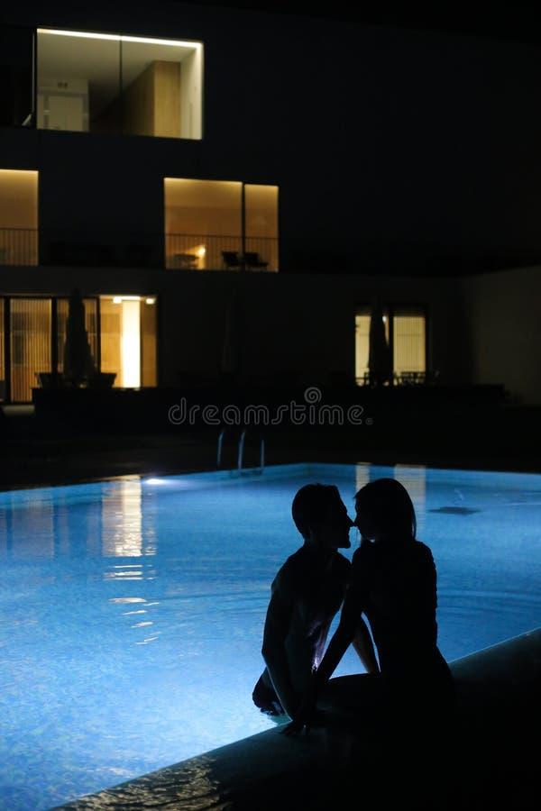 Romantiska par som kysser på pölen i natten royaltyfri bild
