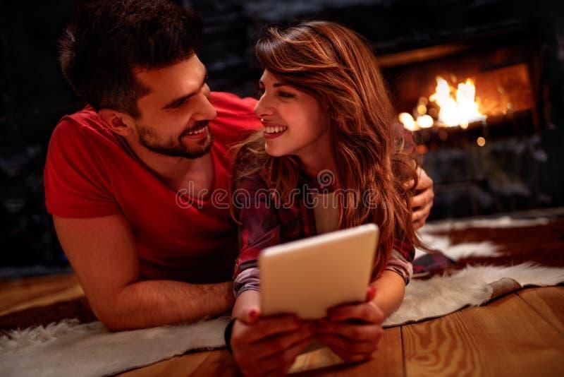 Romantiska par som lägger på golv och hemma använder minnestavlan royaltyfri bild
