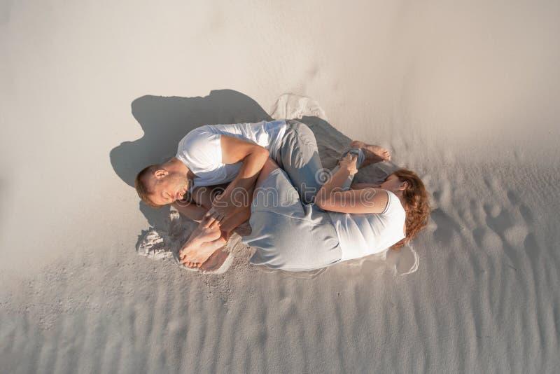Romantiska par som lägger på vit sand i öken arkivfoto