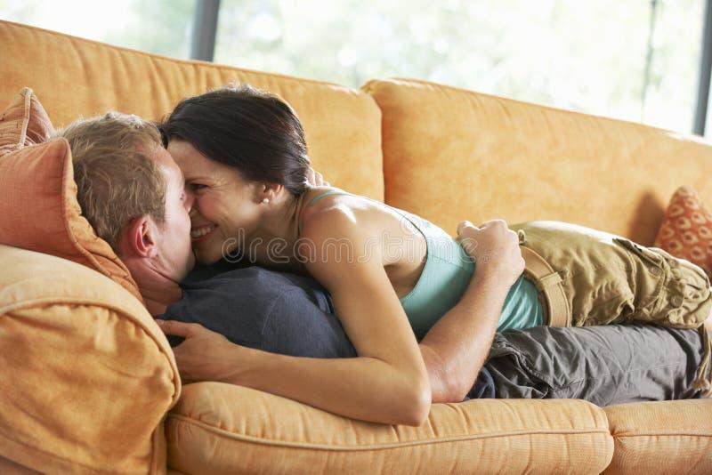 Romantiska par som ligger på Sofa At Home royaltyfri foto