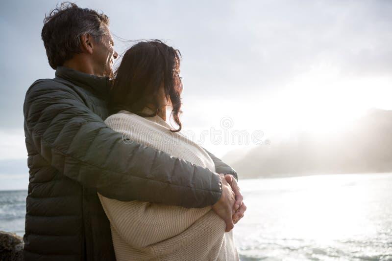Romantiska par som omfamnar sig på stranden arkivfoto