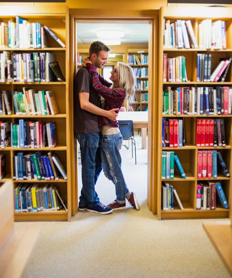 Romantiska par som omfamnar vid bokhyllor i arkiv royaltyfri foto