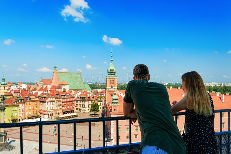 Romantiska par som ser den Sigismund kolonnen på slottfyrkant i den gamla staden av Warszawa i Polen royaltyfri bild