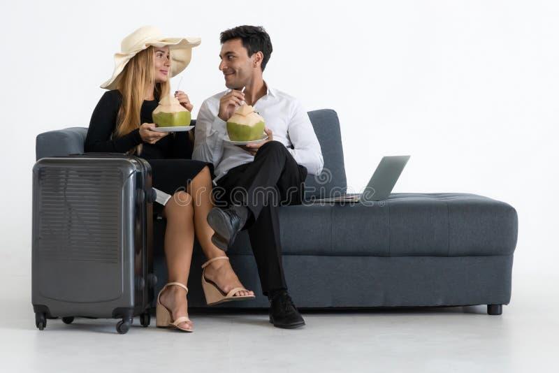 Romantiska par som sitter och dricker kokosnötvatten på soffan Resa resv?skan med seascapeinsida royaltyfri bild