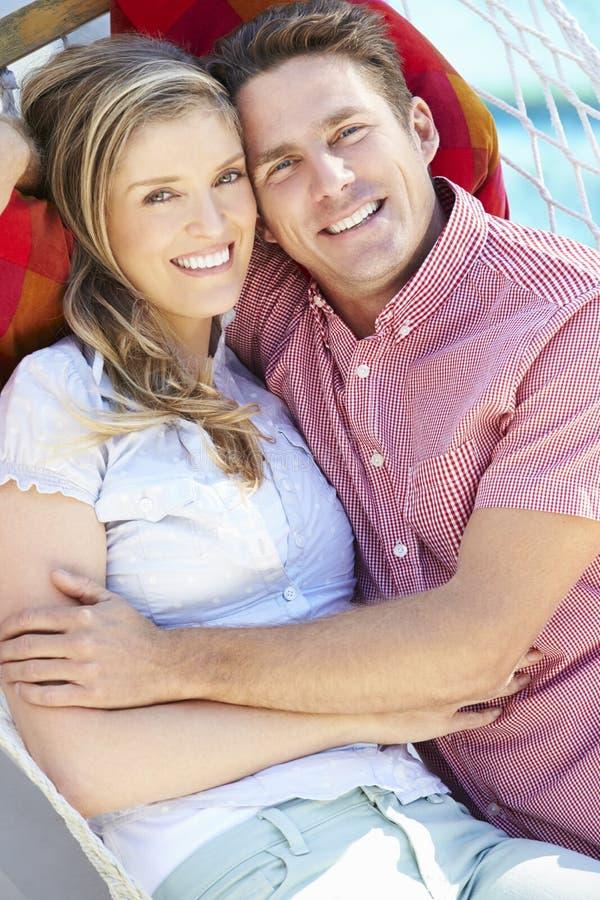 Romantiska par som tillsammans kopplar av i trädgårds- hängmatta royaltyfria bilder