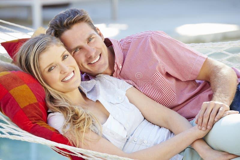 Romantiska par som tillsammans kopplar av i trädgårds- hängmatta royaltyfri bild