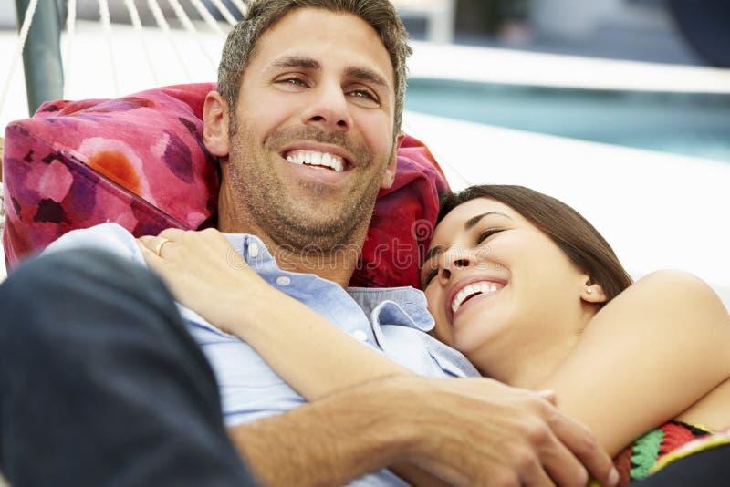 Romantiska par som tillsammans kopplar av i trädgårds- hängmatta fotografering för bildbyråer