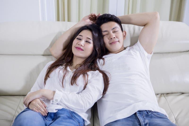 Romantiska par som tillsammans sover p? soffan royaltyfri fotografi