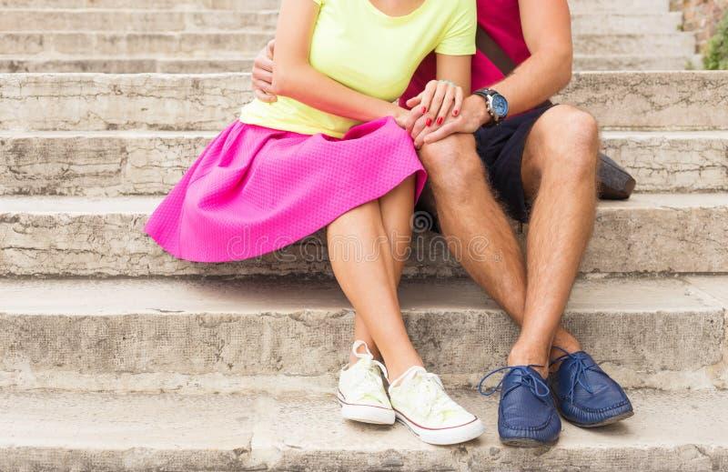Romantiska par som tillsammans utomhus sitter på trappa arkivfoto