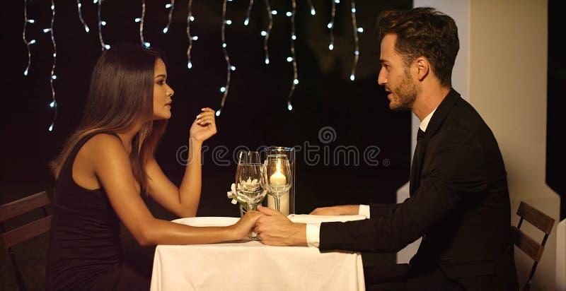Romantiska par som tycker om en aftonmatställe arkivfoton