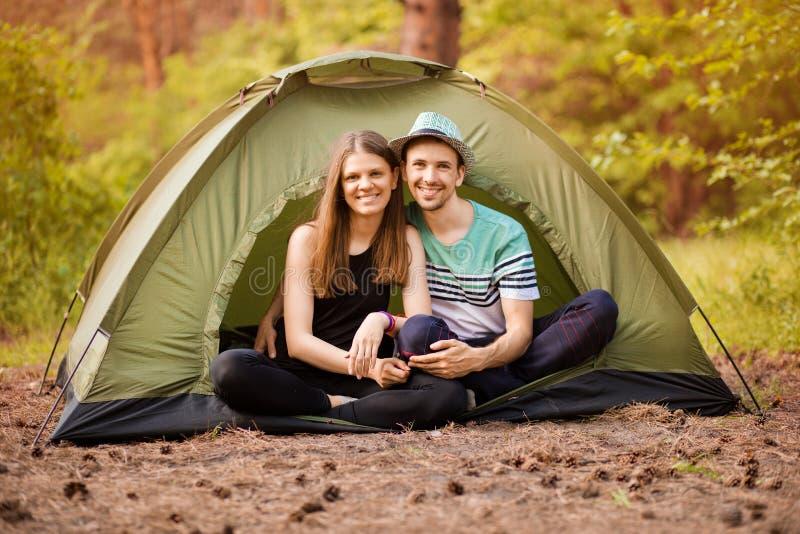 Romantiska par som utomhus campar och sitter i t?lt Lycklig man och kvinna på romantisk semester arkivbild