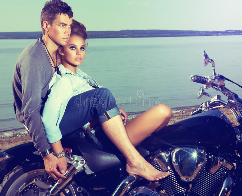 Romantiska par som vilar på lakekusten, motorbike royaltyfri foto