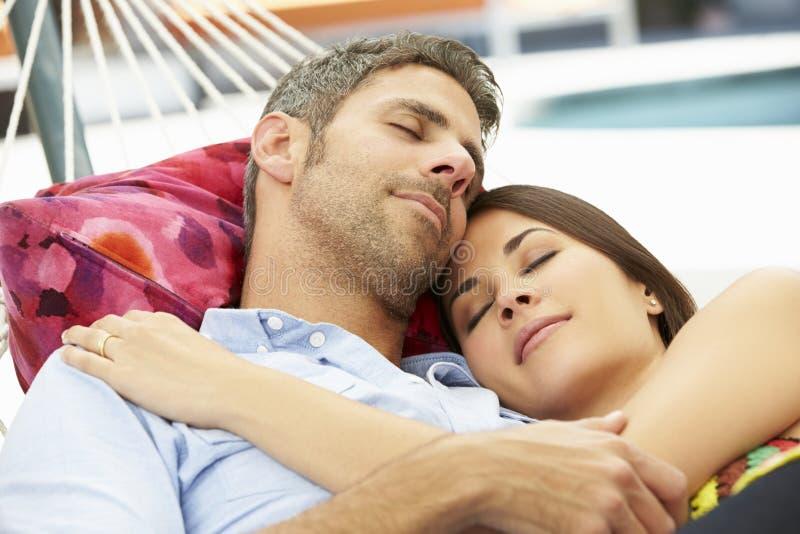 Romantiska par sovande i trädgårds- hängmatta tillsammans arkivfoton
