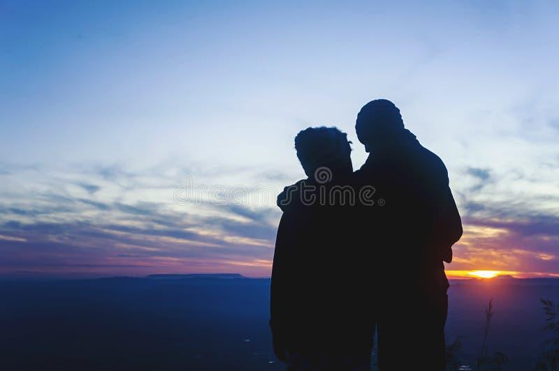 Romantiska parvänner kram och kyss för kontur på den färgrika solnedgången fotografering för bildbyråer