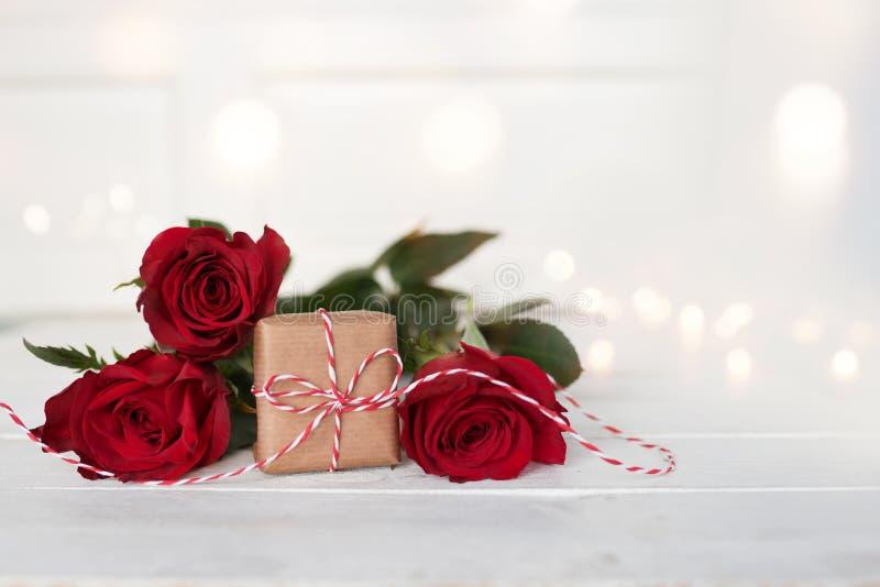 Romantiska röda rosor med en gåva på vit bakgrund arkivfoto