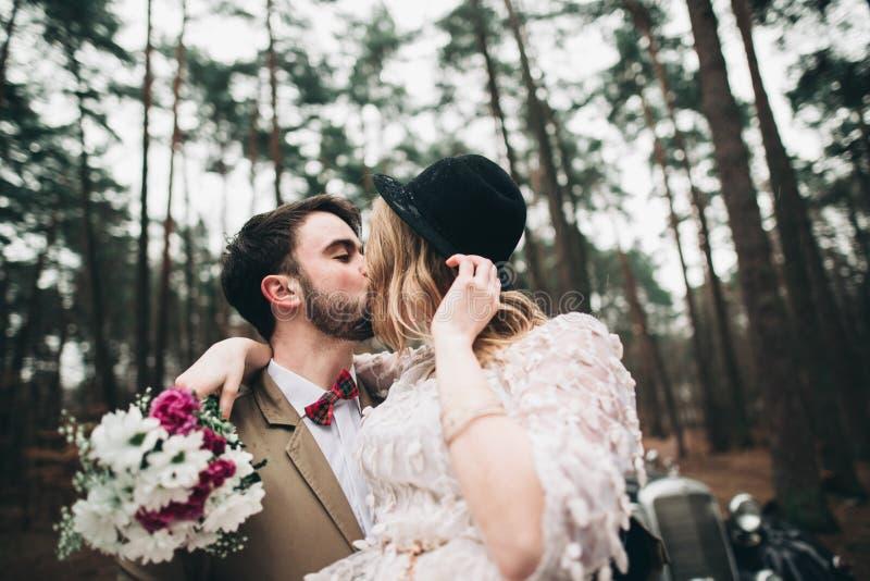 Romantiska sagabrölloppar som kysser och omfamnar i pinjeskog nära den retro bilen royaltyfria bilder