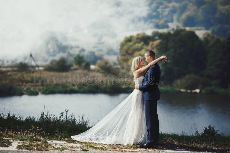 Romantiska sagapar som kramar med den härliga sjön i backgro arkivfoton