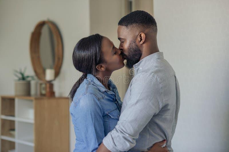 Romantiska unga afrikansk amerikanpar som hemma kysser royaltyfria bilder