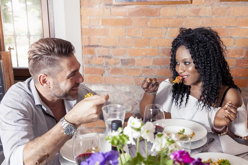 Romantiska unga par som äter middag på en trevlig restaurang fotografering för bildbyråer