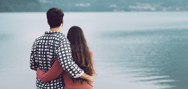 Romantiska unga par som kramar på sjön arkivbilder