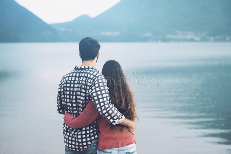 Romantiska unga par som kramar på sjön arkivbild
