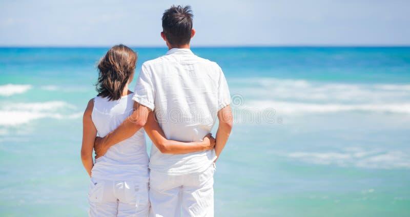 Romantiska unga par tillsammans på stranden arkivfoton