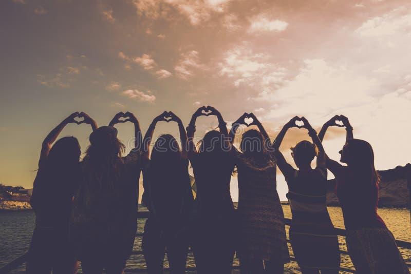 Romantiskt begrepp för flickor göra hjärtor med händer som är alla tillsammans i förhållande och kamratskap framme av en härlig s royaltyfri foto
