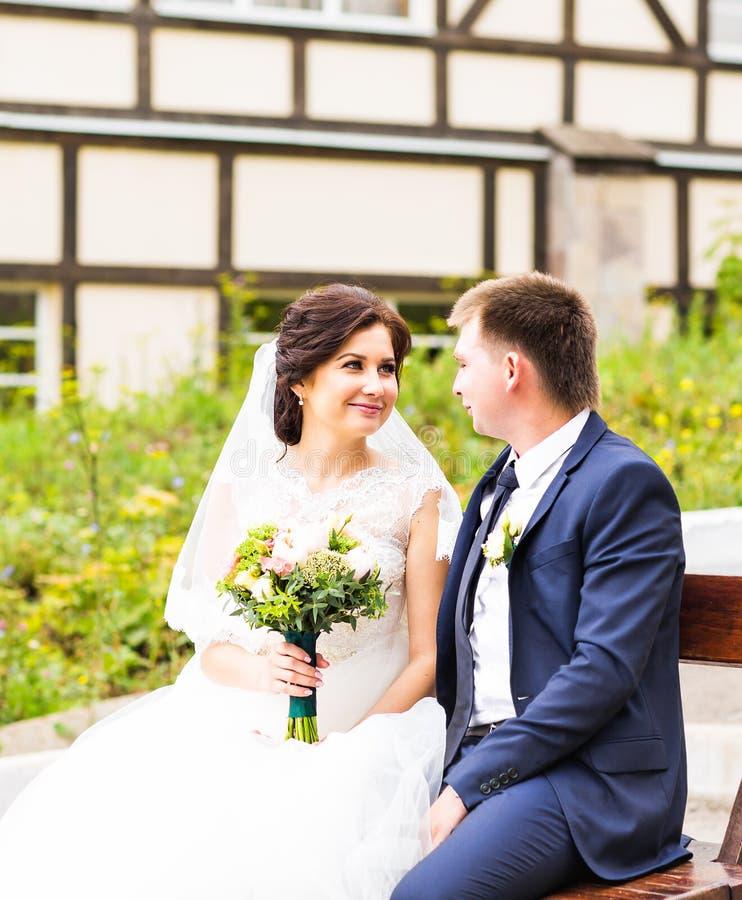 Romantiskt bröllopparsammanträde på en bänk i parkera royaltyfri fotografi