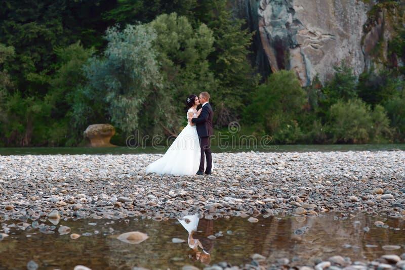 Romantiskt gifta sig ögonblick av nygift personpar som kramar nära den blåa bergfloden, sinnlig brudgum som bakifrån omfamnar urs arkivfoton