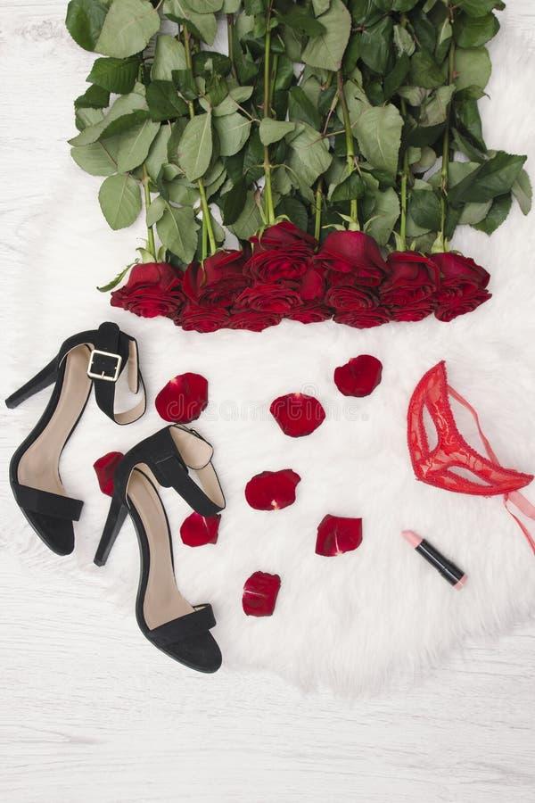 Romantiskt karnevalbegrepp Röd karnevalmaskering, en bukett av röda rosor, svarta skor med häl, läppstift och spridda kronblad på royaltyfri foto