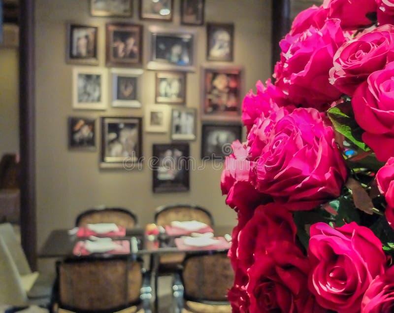 Romantiskt matställebegrepp, bukett av röda rosor med suddighet som äter middag tabellen i bakgrund för Valentine Event arkivbild