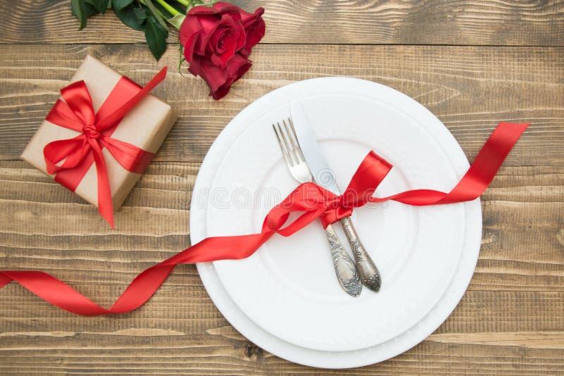 Romantiskt matställebegrepp Festlig tabellinställning för valentindag på träbakgrund Röd ros och romantikergåva Top beskådar arkivfoto