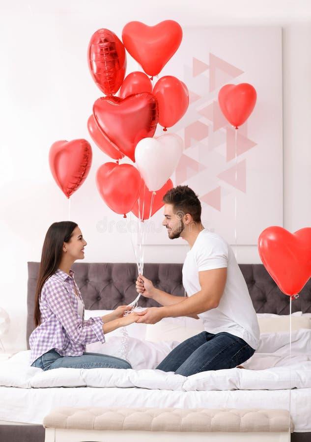 Romantiskt par med hjärtformade ballonger Alla hjärtans dag royaltyfria bilder