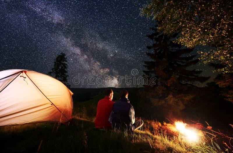 Romantiskt parsammanträde för bakre sikt i tältläger vid brand under natthimmel som beströs med stjärnor och den mjölkaktiga väge royaltyfri fotografi
