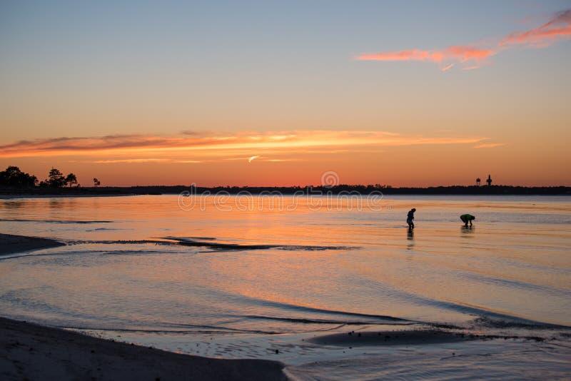 Romantiskt samla för man- och kvinnakonturskal på stranden på solnedgången arkivfoto
