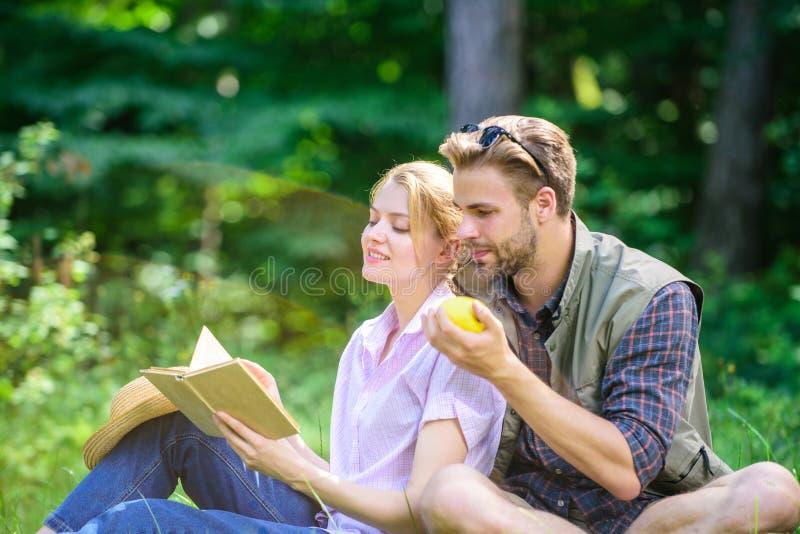 Romantyczna data przy zieloną łąką Para w miłości wydaje czas wolny czytelniczą książkę Par soulmates przy romantyczną datą przyj zdjęcie royalty free
