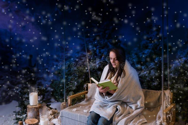 Romantyczna kobieta czyta książkę podczas gdy siedzący na wrapp i huśtawce zdjęcia stock