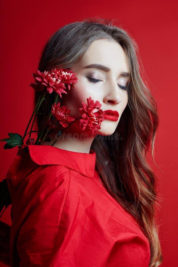 Romantyczna kobieta z d?ugim blondynka w?osy, kwiatami w jej r?kach w czerwieni sukni i, g?adka czysta sk?ra zdjęcia royalty free