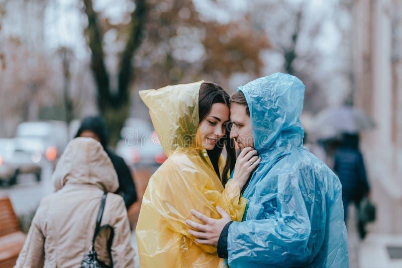 Romantyczna kochaj?ca para, facet i jego dziewczyna w deszczowach, stoimy twarz w twarz na ulicie w deszczu obrazy stock