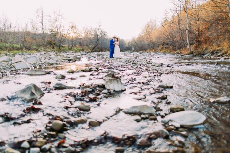 Romantyczna młoda bridal para pije wino na skalistym otoczaka brzeg rzeki z lasowymi wzgórzami i strumieniem obrazy royalty free
