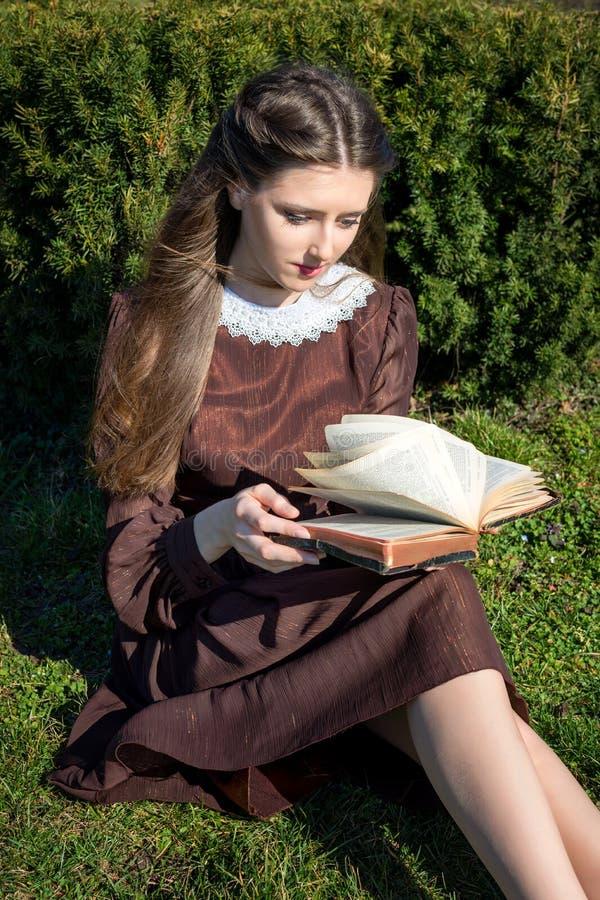 Romantyczna młoda kobieta czyta książkę w ogrodowym obsiadaniu na trawie Relaksuje plenerowego czasu pojęcie zdjęcia stock