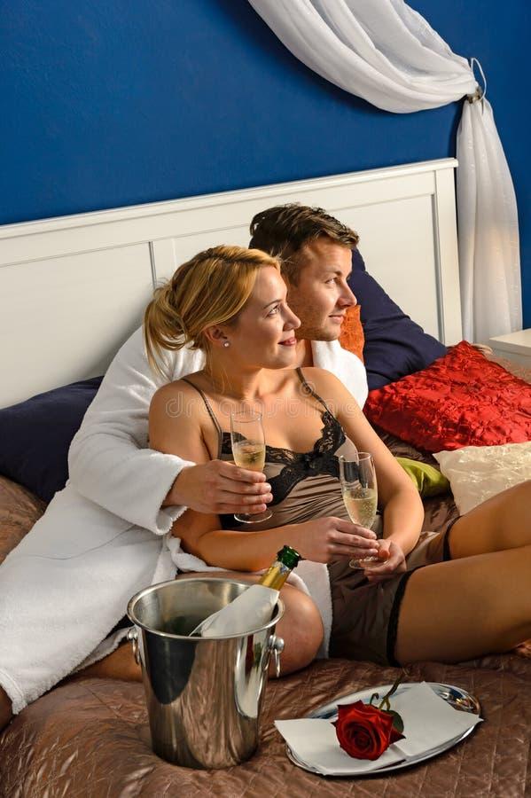 Romantyczna para cuddling łóżkową szampańską odświętność zdjęcia stock