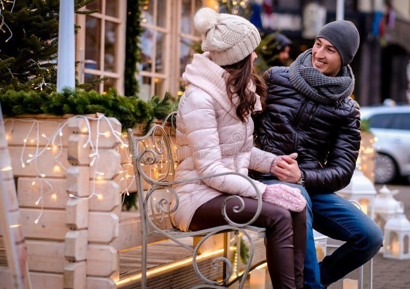 Romantyczna para jest ubranym ciepłego odzieżowego obsiadanie na ławce w wieczór ulicie dekorował z pięknymi światłami, opowiada  fotografia stock